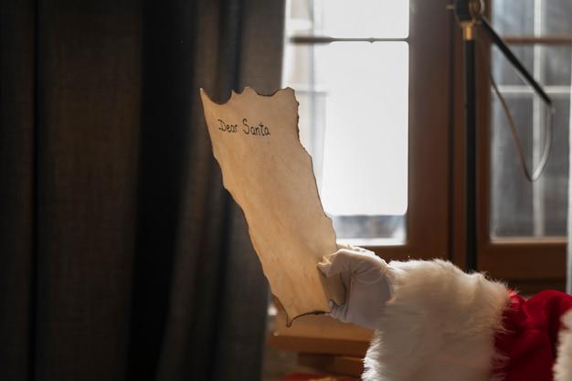 Mano di babbo natale in possesso di una lettera indirizzata a lui