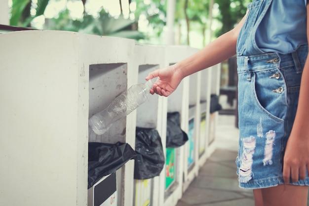 Mano di bambini che getta la bottiglia di plastica vuota nel cestino riciclaggio al parco