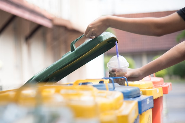 Mano di bambini che getta la bottiglia di plastica vuota nella spazzatura.