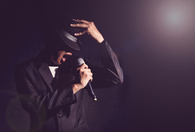 Mano di cantante che tiene il microfono e cantando su sfondo nero