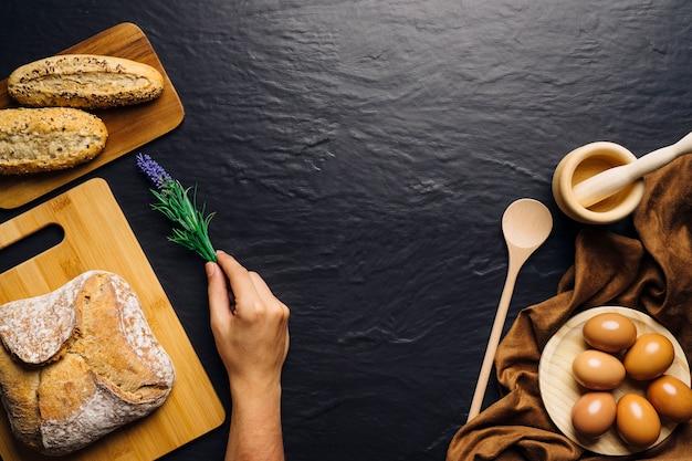 Mano di collocare fiore accanto al pane