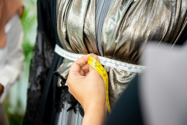 Mano di designer femminile utilizzando un nastro di misurazione
