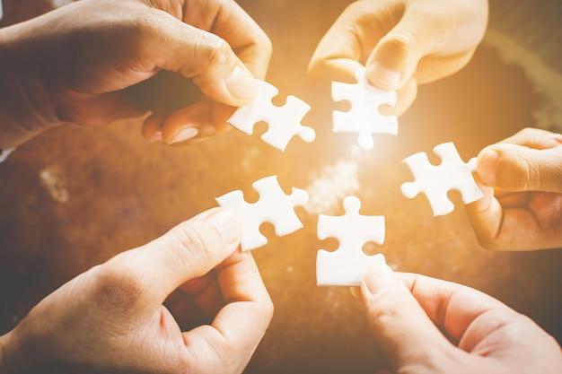 Mano di diverse persone che collegano jigsaw puzzle. concetto di partnership e lavoro di squadra nel mondo degli affari