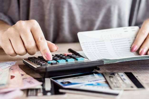 Mano di donna calcolando i soldi sul conto di risparmio