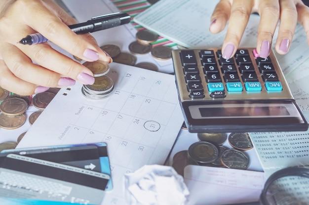 Mano di donna calcolando il pagamento con carta di credito alla data di scadenza