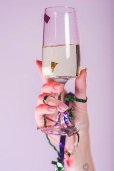 Mano di donna che tosta il bicchiere di champagne
