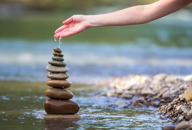 Mano di donna che versa acqua su pietre equilibrate come piramide