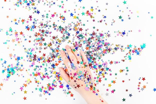 Mano di donna con coriandoli di stelle di colore festivo