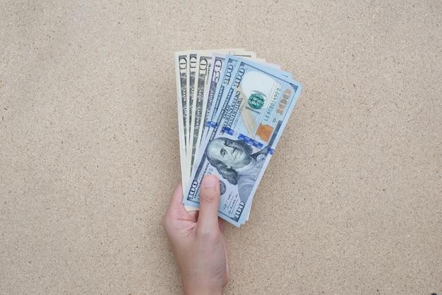 Mano di donna con dollari sul tavolo.