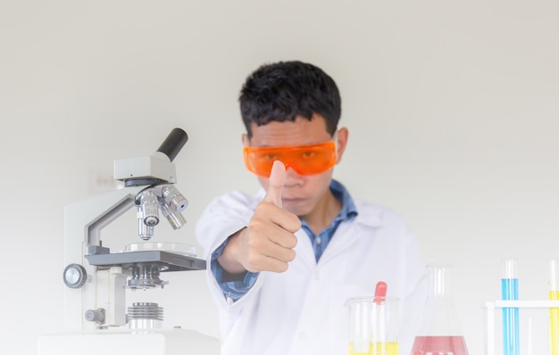 Mano di giovane scienziato che dà pollice in su come segno di successo, facendo test chimici in laboratorio
