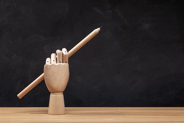 Mano di legno che tiene una matita. sfondo lavagna. ritorno a scuola o concetto di disegno.