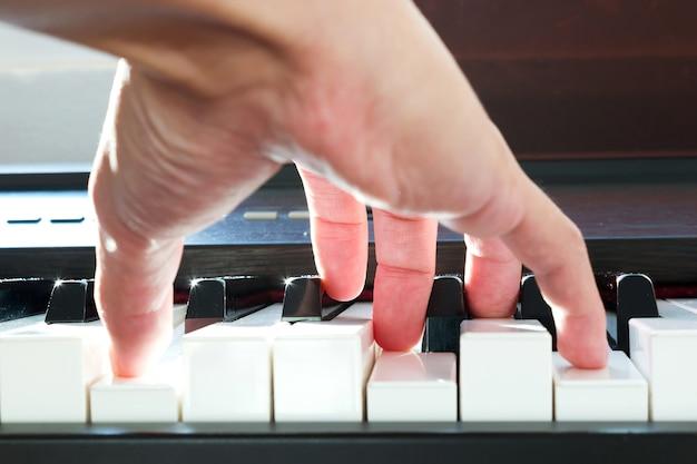 Mano di mand suonare il piano. basso punto di vista. luce del sole e bokeh. sfondo artistico