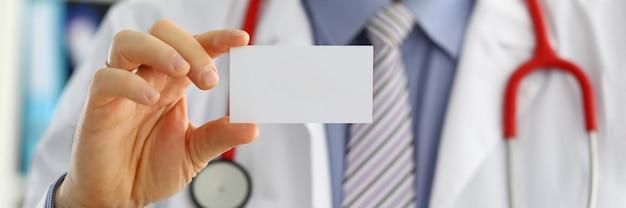 Mano di medico di medicina maschio che tiene biglietto da visita in bianco.