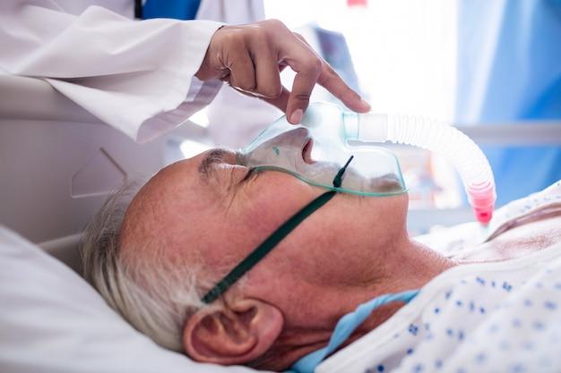 Mano di medico femminile che mette maschera di ossigeno sul viso paziente