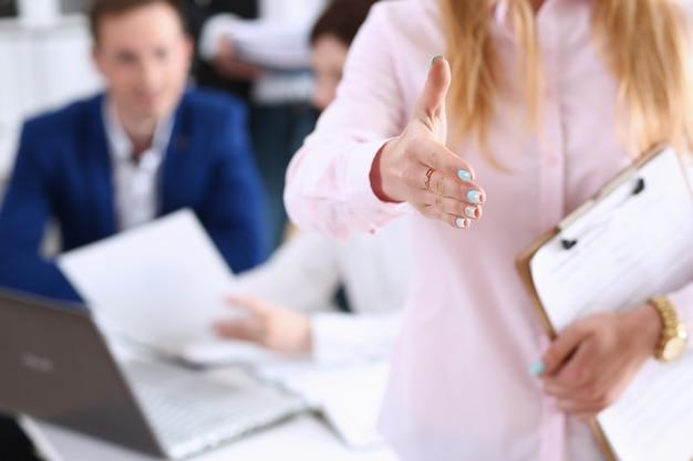 Mano di offerta della donna di affari da stringere come ciao in primo piano dell'ufficio