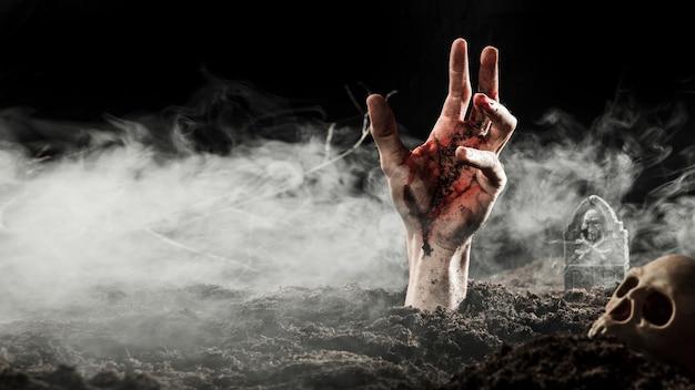 Mano di sangue che spunta da terra nella nebbia