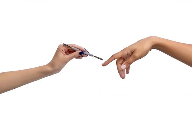 Mano di un maestro con lo strumento manicure e una mano di un cliente