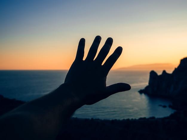 Mano di un turista al tramonto sullo sfondo del mare e delle montagne in natura