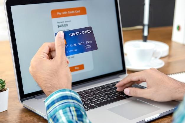 Mano di una carta di credito della tenuta dell'uomo che effettua pagamento online con il computer portatile