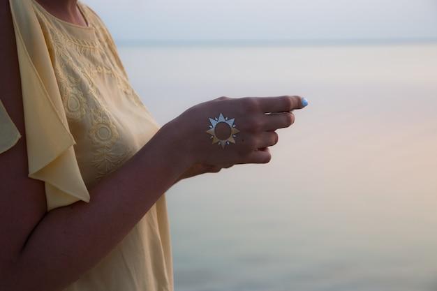 Mano di una donna che medita in una posa di yoga sulla spiaggia al tramonto