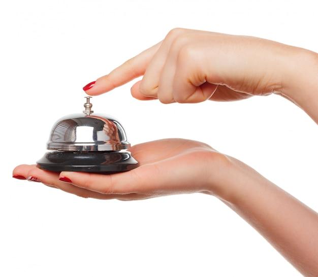 Mano di una donna che usando una campana dell'hotel isolata