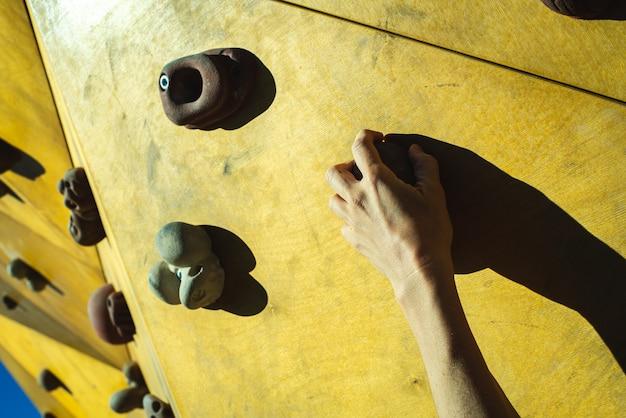 Mano di una persona che cerca di arrampicarsi sulla fixie di una parete da arrampicata