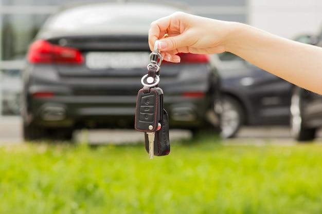 Mano di una ragazza con una chiave di auto in mano, contro uno sfondo di auto nuova