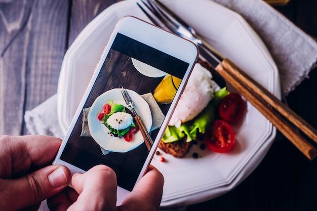 Mano di uomini che prendono cibo per foto con lo smartphone mobile
