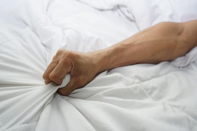 Mano di uomini che tirano lenzuola bianche in estasi, orgasmo.
