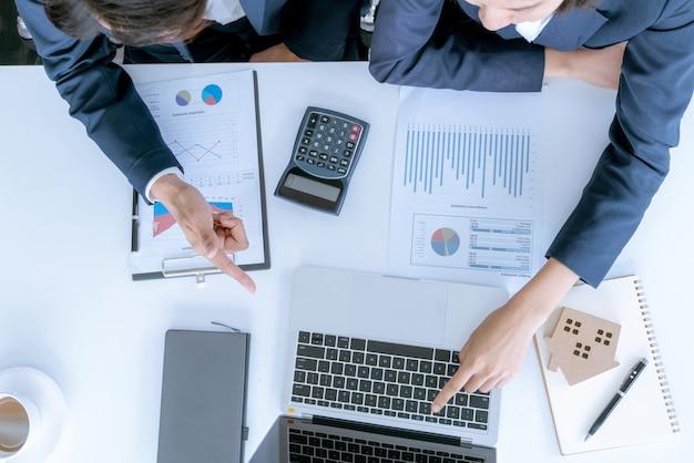 Mano di uomini d'affari calcolando interessi, imposte e profitti da investire nel settore immobiliare
