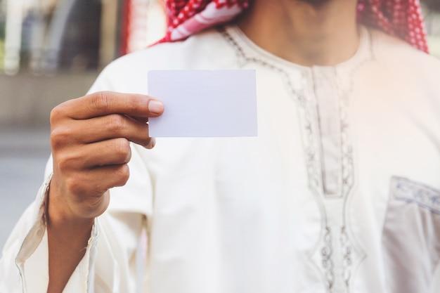Mano di uomo d'affari arabo che mostra biglietto da visita