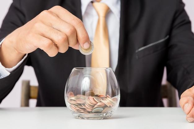 Mano di uomo d'affari che mette le monete sul vetro