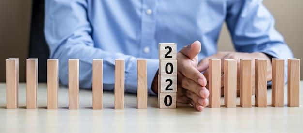 Mano di uomo d'affari fermando la caduta di 2020 blocchi di legno.