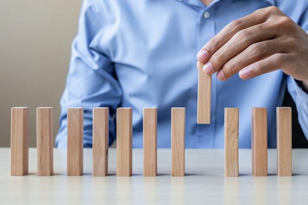 Mano di uomo d'affari tirando o posizionando blocchi di legno o domino
