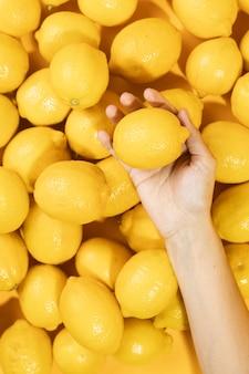 Mano di vista superiore che tiene limonata cruda