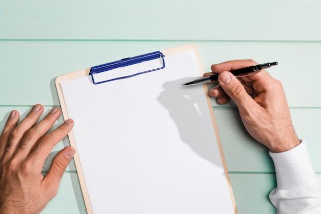 Mano di vista superiore che tiene una penna sopra la lavagna per appunti dello spazio della copia