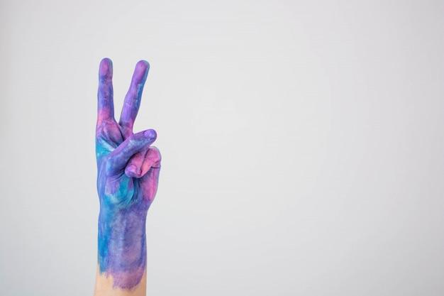 Mano dipinta colorata blu e rosa che gesturing il segno di pace