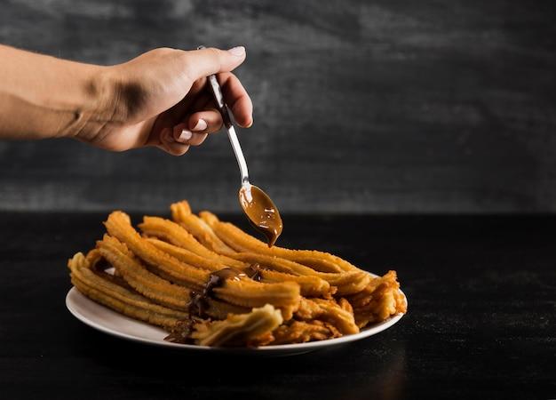 Mano e cucchiaio con deliziosi churros fritti