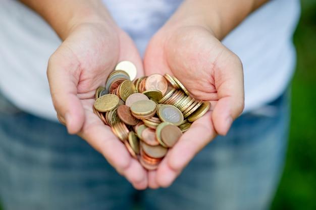 Mano e moneta d'argento, concetto di risparmio di denaro per l'operazione commerciale