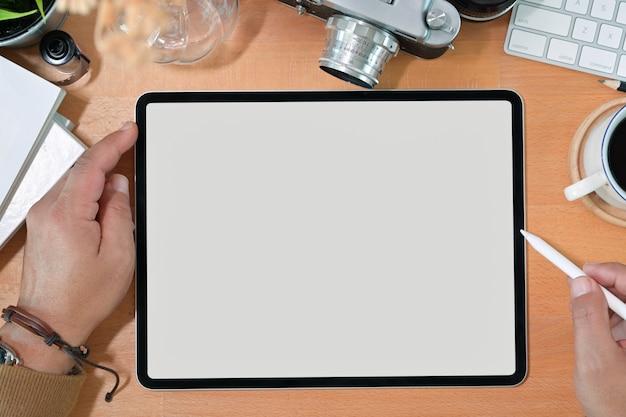 Mano elegante creativa che tiene compressa e matita del disegno dello schermo in bianco