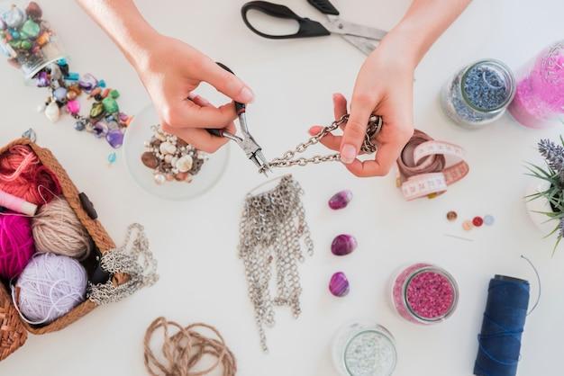 Mano facendo e tagliando la catena metallica sulla scrivania bianca con perline