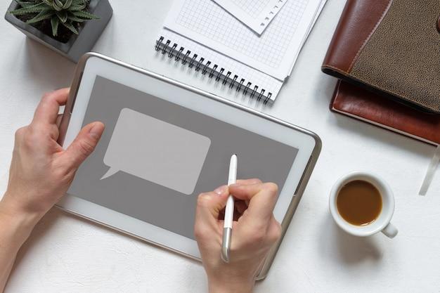Mano facendo uso dello schermo in bianco di tocco digitale del dito della compressa sulla tavola di lavoro dello scrittorio