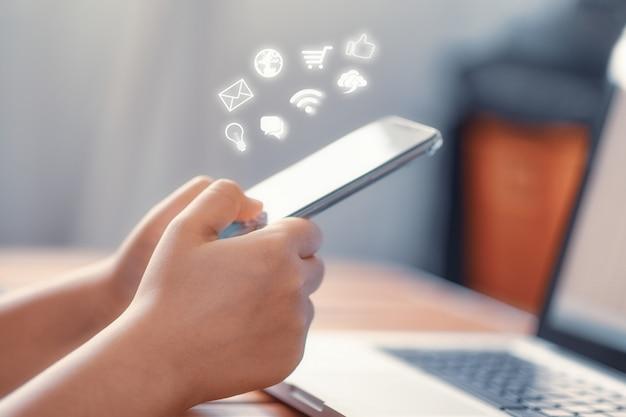 Mano facendo uso dello smart phone con il concetto di media sociali