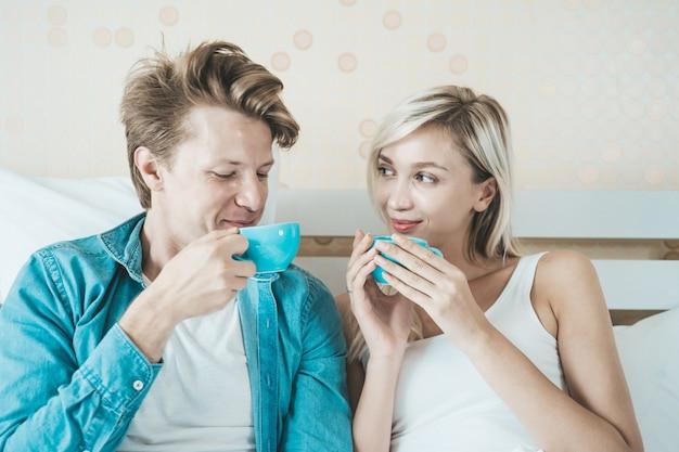 Mano felice delle coppie che tiene tazza e che beve caffè di mattina