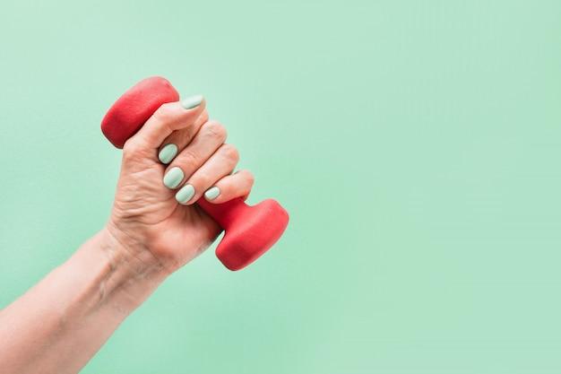 Mano femmina con manubri rosso su sfondo verde attrezzature per lo sport fitness