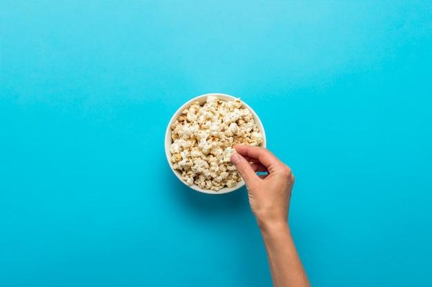 Mano femminile che cattura popcorn da una tazza bianca su sfondo blu. concetto di guardare un film con popcorn, attività ricreative per mangiare popcorn. vista piana, vista dall'alto