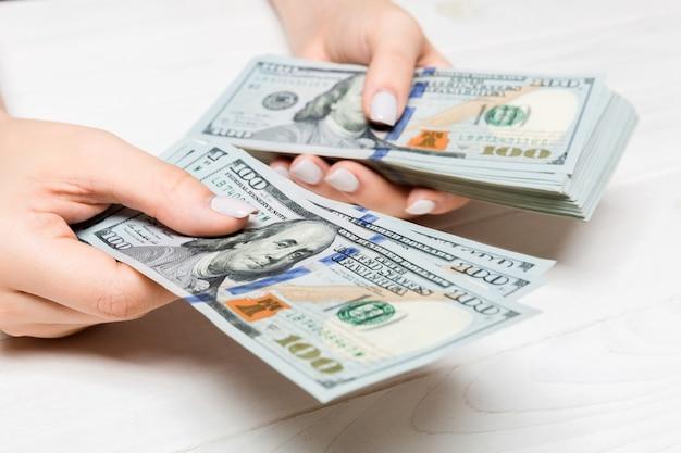 Mano femminile che dà cento banconote in dollari su superficie di legno. vista prospettica del concetto di ricchezza