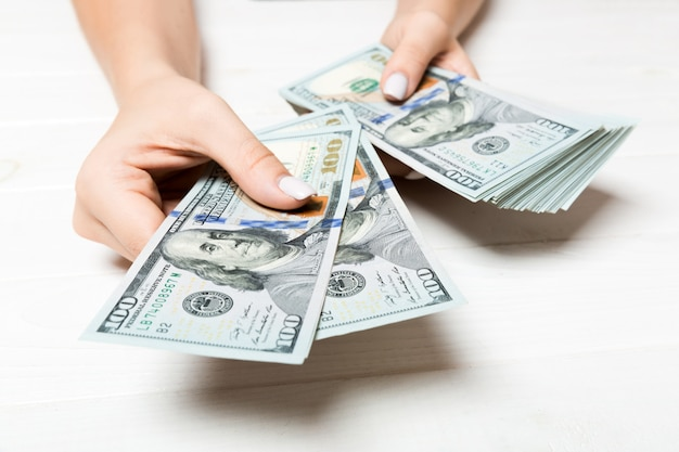Mano femminile che dà le banconote da cento dollari su di legno. ricchezza vista prospettica