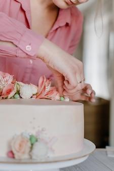 Mano femminile che decora la torta di compleanno rosa di nozze del fiore sul supporto.