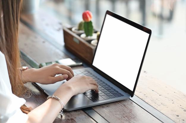 Mano femminile che lavora con il suo computer portatile sulla tavola di legno